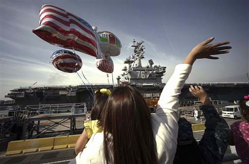 FILE - In this Oct. 1, 2015 file photo, family members of sailors wave as the U.S. Navy aircraft carrier USS Ronald Reagan arrives at a U.S. Navy base in Yokosuka, Japan south of Tokyo. The U.S. Pacific Fleet is smaller than it was in the 1990s, helping fuel a debate about whether the U.S. has enough ships to meet challenges posed by fast-growing and increasingly assertive Chinese naval forces. (AP Photo/Eugene Hoshiko, File)