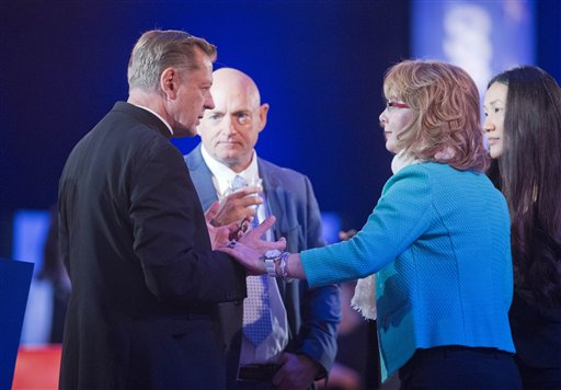 Father Michael Pfleger, left, Pastor at Saint Sabina Catholic Church in Chicago, speaks with former Rep. Gabby Giffords, D-Ariz., right, and her husband Mike Kelly, center, right, before taking their seats for President Barack Obama's televised town hall at George Mason University in Fairfax, Va., Thursday, Jan. 7, 2016. Obama's proposals to tighten gun controls rules may not accomplish his goal of keeping guns out of the hands of would-be criminals and those who aren't legally allowed to buy a weapon. In short, that's because the conditions he is changing by executive action are murkier than he made them out to be. (AP Photo/Pablo Martinez Monsivais)