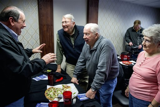 In this Jan. 6, 2016, photo, Republican presidential candidate, former Arkansas Gov. Mike Huckabee speaks with visitors during a campaign stop at Tony's La Pizzeria in Cedar Falls, Iowa. Running as an underdog presidential candidate isn't always glamorous. You speak to half-filled halls and small rooms, low-key rallies. Among those hoping for an Iowa winter miracle are Huckabee, 2008 winner of the caucuses, and former Pennsylvania Sen. Rick Santorum, winner in 2012. Also looking for political salvation in either first-to-vote Iowa or in the New Hampshire primary are Kentucky Sen. Rand Paul and former technology executive Carly Fiorina. (AP Photo/Andrew Harnik)