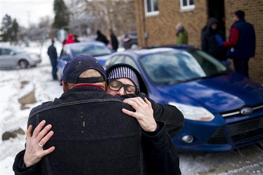 """St. Clair Shores resident Terra Castro embraces Pastor Bobby Jackson outside of his church as she openly prays for him and his community in reflection on the state of emergency in Flint, Mich., while dropping off more than 500 cases of bottled water with about 20 Detroit-based volunteers on Saturday, Jan. 16, 2016, at Mission of Hope on Flint's north side. """"It's overwhelming. The magnitude of the issue and the magnitude of love and compassion people hold for others is so apparent here. Our cities (Flint and Detroit) are very bold, helpful and caring. People who cannot afford to give water are doing it, even though they have issues of their own unresolved,"""" Castro said. """"We're a pretty sad state. It's truly unfortunate that we're surrounded by water with the Great Lakes and we have to worry about water in Flint.""""  (Jake May/The Flint Journal-MLive.com via AP)"""