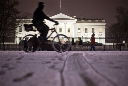 A bicyclist rides past the White House during evening snowfall in Washington,Wednesday, Jan. 20, 2016. As Washington prepares for this weekend's snowstorm, now forecast to reach blizzard conditions, a small clipper system pushed through the region Wednesday night causing massive delays and issues on the roads.(AP Photo/Pablo Martinez Monsivais)