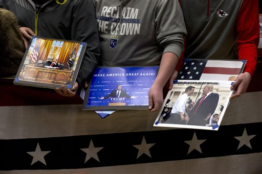 Supporters hold photos of Republican presidential candidate Donald Trump including one of Trump with Republican presidential candidate, Sen. Ted Cruz, R-Texas, in hopes of getting them autographed during a campaign event at the Roundhouse Gymnasium, Tuesday, Jan. 26, 2016, in Marshalltown, Iowa. (AP Photo/Mary Altaffer)
