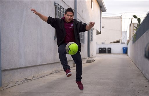 Marvin Velasco, 15, practices soccer outside his new home in Los Angeles on Monday, Jan. 11, 2016. Velasco's perilous journey from Guatemala included crossing a river, even though he doesn't swim, and getting lost at night in a frigid desert. Once in the U.S., he turned himself in to U.S. Border Patrol agents in Reynosa, Texas, and was sent to a shelter run by the U.S. Department of Health and Human Services' Office of Refugee Resettlement. (AP Photo/Mark J. Terrill)