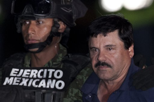 """Mexican drug lord Joaquin """"El Chapo"""" Guzman is escorted by soldiers and marines to a waiting helicopter, at a federal hangar in Mexico City, Friday, Jan. 8, 2016. The world's most wanted drug lord was recaptured by Mexican marines Friday, six months after he fled through a tunnel from a maximum security prison in an escape that deeply embarrassed the government and strained ties with the United States.(AP Photo/Marco Ugarte)"""