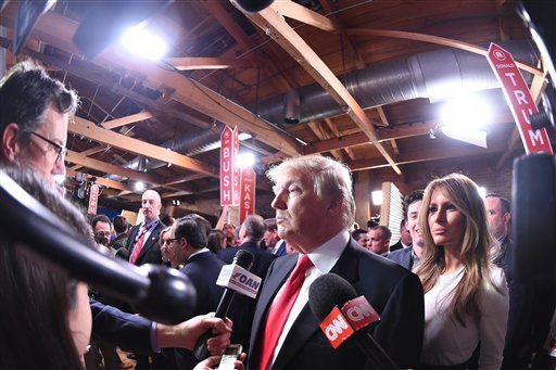 Republican presidential candidate, businessman Donald Trump with his wife Melania Trump at right, speaks to the media in the spin room after the CBS News Republican presidential debate at the Peace Center, Saturday, Feb. 13, 2016, in Greenville, S.C. (AP Photo/Rainier Ehrhardt)
