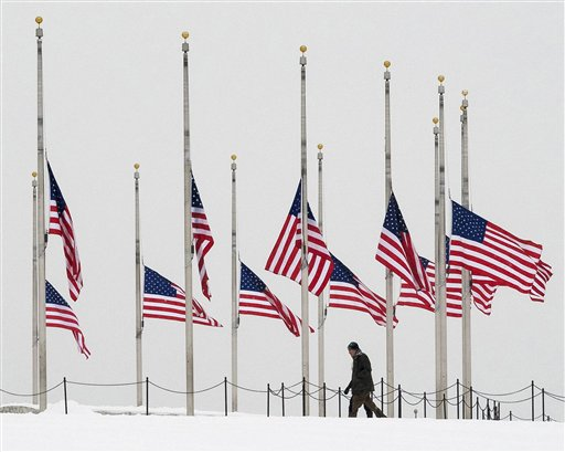 Visitors to the Washington Monument walk past flags flying a half-staff in honor of Supreme Court Justice Antonin Scalia on a wintry Presidents Day holiday in Washington, Monday, Feb, 15, 2016. (AP Photo/J. David Ake)