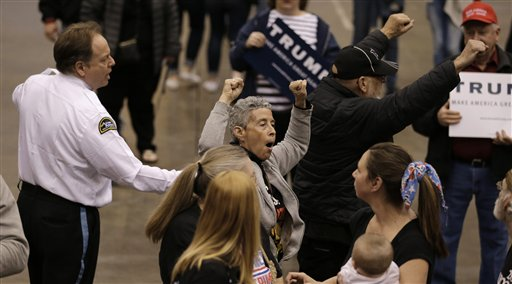Protesters are escorted out of the building as Republican presidential candidate, Donald Trump speaks at a campaign rally at the I-X Center Saturday, March 12, 2016, in Cleveland. (AP Photo/Tony Dejak)