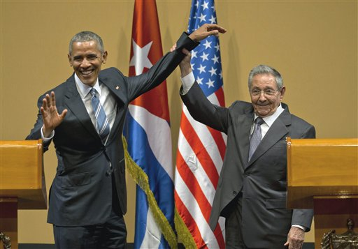 Cuban President Raul Castro, right,  lifts up the arm of President Barack Obama at the conclusion of their joint news conference at the Palace of the Revolution, Monday, March 21, 2016, in Havana, Cuba. (AP Photo/Ramon Espinosa)