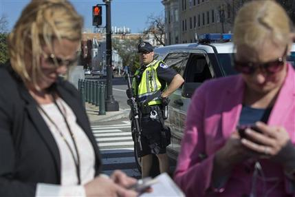 A Capitol Police officer watches as members of the media work in the foreground on Capitol Hill in Washington, Monday, March 28, 2016. Capitol Police officers say a man was shot by police after drawing a weapon at a U.S. Capitol checkpoint. He was taken to the hospital.  (AP Photo/Jacquelyn Martin)