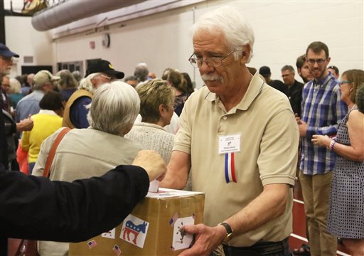 Dennis Smyth accepts paper ballots from voters at the Laramie County Democratic Caucus held Saturday, April 9, 2016, in Cheyenne, Wyo. (Shawn Havel/The Wyoming Tribune Eagle via AP)