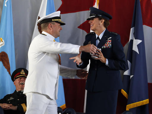 Navy Admiral William E. Gortney, the outgoing commander of the North American Aerospace Defense Command and U.S. Northern Command, hugs the incoming commander, Air Force Gen. Lori J. Robinson, also giving her his Denver Broncos mug, during the change of command ceremony at Peterson Air Force Base, in Colorado Springs, Colo., Friday, May 13, 2016. Gen. Robinson is the first woman to lead a top-tier U.S. military command after taking charge Friday at NORAD and USNORTHCOM. (AP Photo/Brennan Linsley)