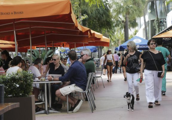 FILE - In this Wednesday, Feb. 3, 2016, file photo, people dine at outdoor cafes and walk along Lincoln Road Mall, a pedestrian area featuring retail shops and restaurants in Miami Beach, Fla. Americans are treating themselves with more restaurant meals after slogging through a dreary seven-year recovery from the worst economic crisis since the Great Depression. Only 42 percent of adults describe the U.S. economy as good, according to a survey released Wednesday, May 18, 2016, by The Associated Press. But nearly two-thirds say their own households are faring well. That divide reflects a country sharply split by political affiliation and education level in the midst of an intensely negative presidential race. (AP Photo/Lynne Sladky, File)