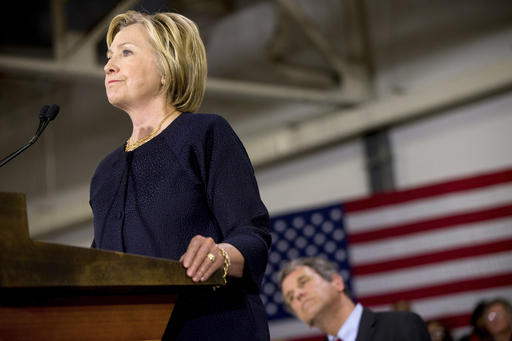 """Democratic presidential candidate Hillary Clinton, left, accompanied by Sen. Sherrod Brown, D-Ohio, right, speaks at a rally at a warehouse for the company """"Team Wendy"""" which produces helmets for military, law enforcement, and rescue teams, in Cleveland, Monday, June 13, 2016. (AP Photo/Andrew Harnik)"""