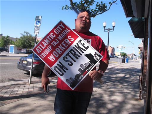 A casino worker carries a picket sign on Thursday June 30, 2016 in Atlantic City N.J. (AP Photo/Wayne Parry)