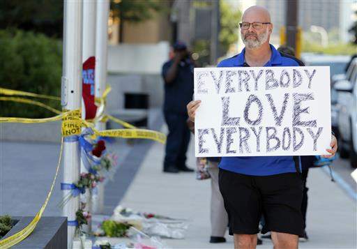 """Chris Bailey walks by a makeshift memorial on Griffin Street holding a sign that reads, """"Everybody Love Everybody"""", Friday, July 8, 2016, in Dallas. (AP Photo/Tony Gutierrez"""