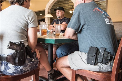 Jeff Coursey, of Paris Texas, center, sits in a restaurant on Saturday, July 9, 2016. Coursey is considering starting a local chapter of Open Carry Texas, which supports the right to openly carry a firearm in public. Seated at the table with him are Bill Wilson, owner of Wilson Combat, an Arkansas gunmaker, and his wife, Joyce Wilson, executive director of International Defensive Pistol Association. (AP Photo/Lisa Marie Pane)