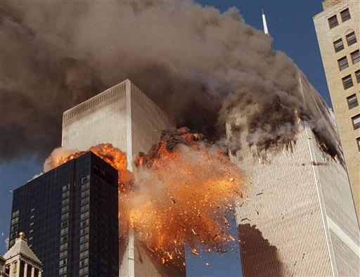 """smoke billows from World Trade Center Tower 1 and flames explode from Tower 2 as it is struck by American Airlines Flight 175, in New York. The government is preparing to release a once-classified chapter of a congressional report about the attacks of Sept. 11, that questions whether Saudi nationals who helped the hijackers with things like finding apartments and opening bank accounts knew what they were planning. House Minority Leader Nancy Pelosi said Friday July 15, 2016, that the release of the 28-page chapter is """"imminent."""" (AP Photo/Chao Soi Cheong, File) MANDATORY CREDIT"""