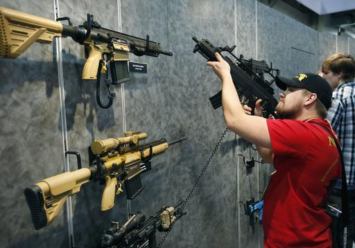 Nolan Hammer looks at a gun at the Heckler & Koch booth at the Shooting, Hunting and Outdoor Trade Show in Las Vegas. Nearly two-thirds of Americans expressed support for stricter gun laws, according to an Associated Press-GfK poll released Saturday, July 23, 2016. A majority of poll respondents favor a nationwide ban on the sale of semi-automatic assault weapons such as the AR-15. (AP Photo/John Locher, File)