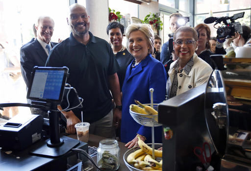 FILE - In this June 10, 2016, file photo, Democratic presidential candidate Hillary Clinton, joined by, from left, Washington City Council member Jack Evans, Uprising Muffin Company owner Donnie Simpson, Washington Mayor Muriel Bowser and Del. Eleanor Holmes Norton, D-D.C., pause during a stop at the store in Washington. (AP Photo/Alex Brandon, File)