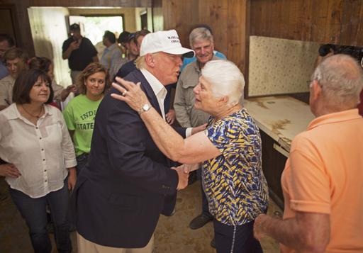Republican presidential candidate Donald Trump, center, comforts flood victim Olive Gordan with her husband Jimmy, right, during tour of their flood damaged home in Denham Springs, La., Friday, Aug. 19, 2016. (AP Photo/Max Becherer)