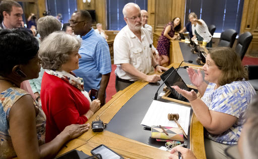 FILE- In this Aug. 9, 2016 file photo, Chairwoman Kathryn Lindley, right, is approached by people during the Guilford County Board of Elections meeting at the Old Guilford County Courthouse in Greensboro, N.C. The swing state of North Carolina could be pushed in a Republican or Democratic direction when the GOP-led State Board of Elections meets Thursday, Sept. 8, 2016 to finalize early voting plans for a third of the state's counties.  (Joseph Rodriguez/News & Record via AP)