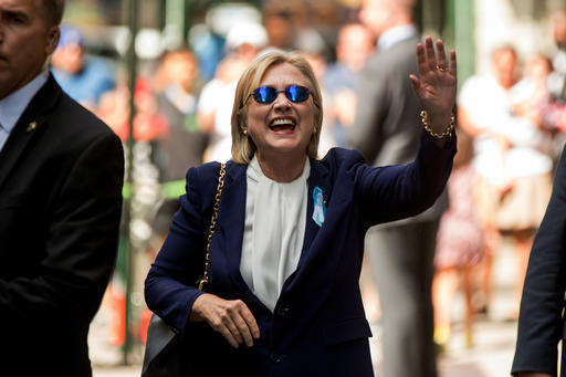 """Democratic presidential candidate Hillary Clinton waves after leaving an apartment building Sunday, Sept. 11, 2016, in New York. Clinton's campaign said the Democratic presidential nominee left the 9/11 anniversary ceremony in New York early after feeling """"overheated."""" (AP Photo/Andrew Harnik)"""