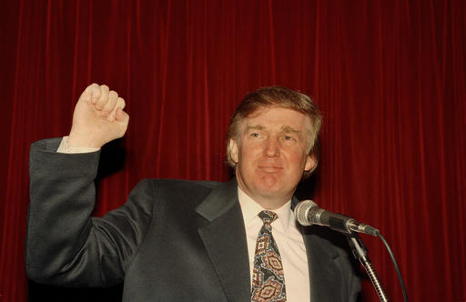 """FILE - In this Dec. 21, 1994 file photo, Donald Trump raises his fist at a news conference New York where he denounced a New York Post report that the Sultan of Brunei is interested in buying the Plaza, the landmark hotel overlooking Central Park. Trump once claimed to be publicity shy, no joke. It's right there in The New York Times of Nov. 1, 1976. In the same article, the 30-year-old real estate developer talks up his millions, showcases his penthouse apartment and Cadillac, and allows a reporter to tag along as he visits job sites and lunches at the """"21"""" club before hopping an evening flight to California for more deal-making. So much for that shy-guy claim.  (AP Photo/Marty Lederhandler)"""