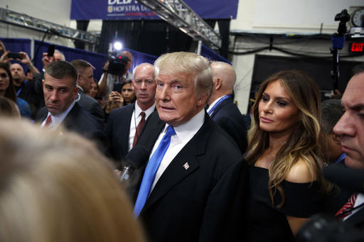 Republican presidential candidate Donald Trump speaks with reporters in the spin room after the first presidential debate against Democratic presidential candidate Hillary Clinton at Hofstra University, Monday, Sept. 26, 2016, in Hempstead, N.Y., as Melania Trump listens at right. (AP Photo/ Evan Vucci)