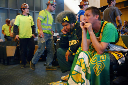 FILE - In this Monday, May 2, 2016 file photo, Seattle SuperSonics fans Kris Brannon, center, and Kenneth Knutsen react to the Seattle City Council's 5-4 no vote against vacating stretch of road where investor Chris Hansen hopes to eventually build an arena that could house an NBA and NHL team. Five women on Seattle's City Council outvoted four men to derail the sports arena project. (Genna Martin/seattlepi.com via AP)