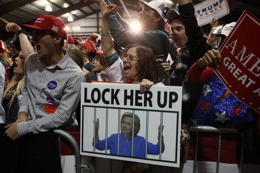 """FILE - In this Monday, Nov. 7, 2016 file photo, supporters of Republican presidential candidate Donald Trump, one holding a sign that reads, """"LOCK HER UP,"""" cheer during a campaign rally in Leesburg, Va. Trump, the president-elect, is calling for unity in words that draw attention precisely because they sound so unlike Trump, the candidate. But many question whether it is possible to reverse the campaign's damage to political discourse and its ripples out to the way Americans speak to and about each other. (AP Photo/ Evan Vucci)"""
