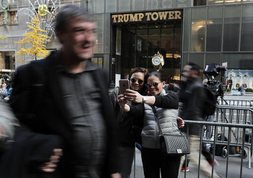 Two women stop to take a selfie from the sidewalk across the street from Trump Tower where President-elect Donald Trump continued meetings with members of his transition team, Wednesday, Nov. 16, 2016, in New York. (AP Photo/Julie Jacobson)