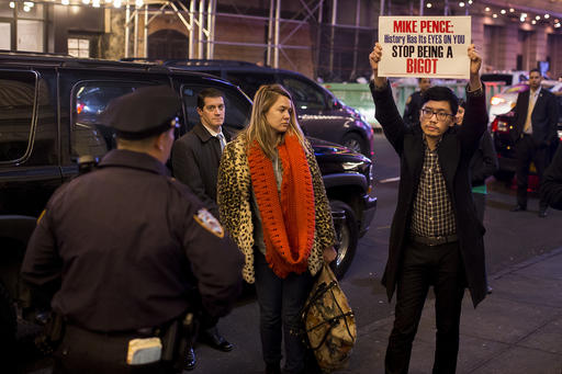 "A protester holds a placard as he waits for Vice President-elect Mike Pence to leave the Richard Rodgers Theatre after a performance of ""Hamilton,"" in New York, Friday, Nov. 18, 2016. (AP Photo/Andres Kudacki)"