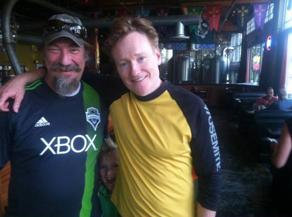 """""""Conan and his son stopped into our Elysian Capitol Hill Brewpub for lunch today! Thanks for showing your support Conan. Cheers! — with David Buhler."""" (Elysian via Facebook)"""