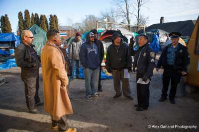 Police talk with the evicted campers Saturday