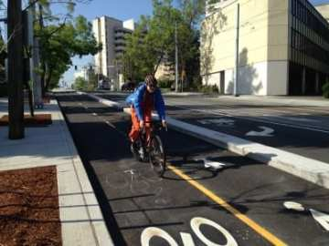 A rider cruises northbound on the newly opened, mostly complete Broadway bikeway. Memo to SDOT: You forgot to remove the hills! Turns out. Riding between Yesler and Howell via Broadway really is uphill both ways. Downhill both ways, though, too. (Image: CHS)
