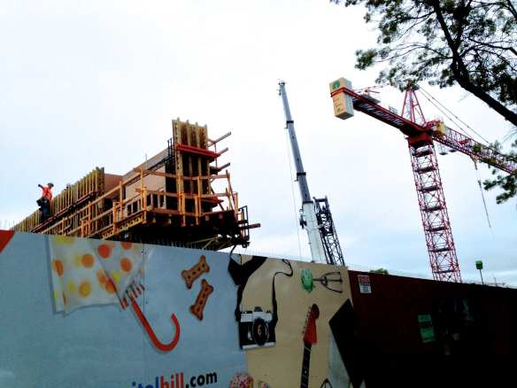 Capitol Hill Station's shell now rises above the Broadway construction walls. Time to say goodbye to the crane. (Image: CHS)