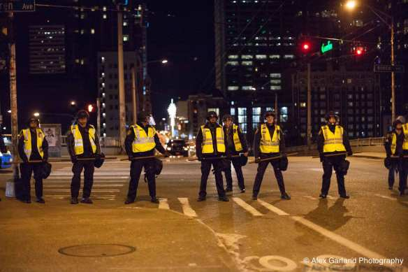 Following the rapid dissolution of the crowd, a line of officers forms to block any large groups of protesters from heading downtown at Pine and Boren (Image: Alex Garland for CHS)