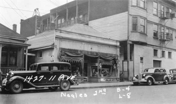 The retail facade hiding a normal house, seen in 1937 as Arai Grocery. Image harvested from Brendan McKeon on HistoryPin, who scanned it at the Washington State Archives.