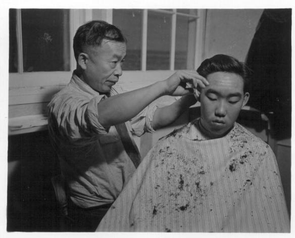 Ted Arai getting his hair cut on December 10, 1943 by Minidoka barber J. K. Kimura. Image WRA no A-762 from UC Berkeley archives.