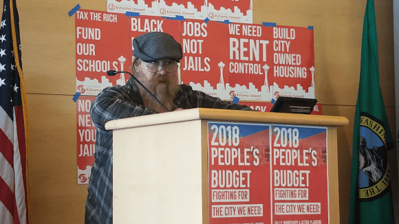 Nickelsville resident and External Affairs Coordinator Sean Smith speaks about the lack of funding present for homeless encampments around Seattle (Image: Ryan Phelan)
