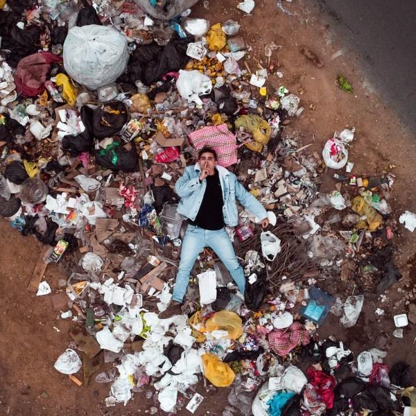 man lying in plastic rubbish: Plastic Free July