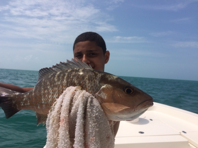 Carlos holding his first mangrove snapper he caught with Capt. Doug on a fishing charter off Marathon.