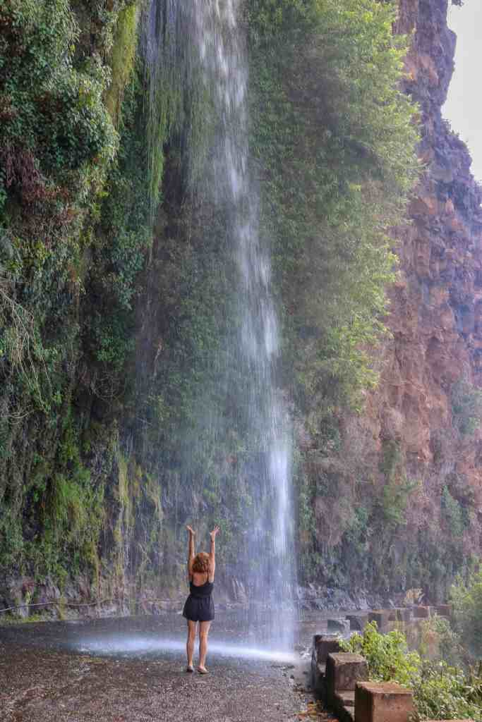 Girl with her hands up standing in the middle of the street under a waterfall