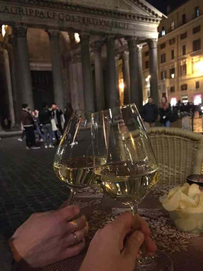Two hands holding two glasses of white wine in front of pantheon
