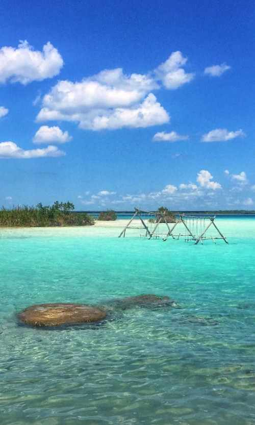 Clear blue water with two swings in it and a clear blue sky with a few white clouds