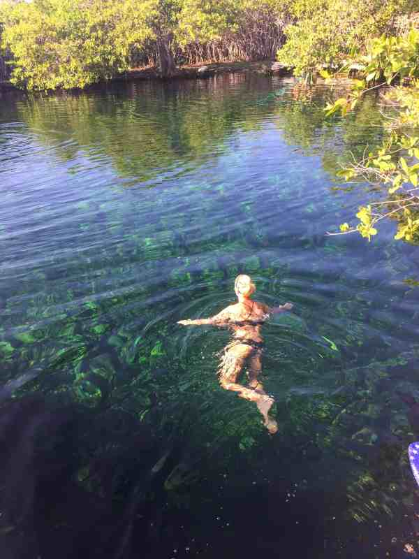 Girl swimming in a cenote with clear blue water in Tulum