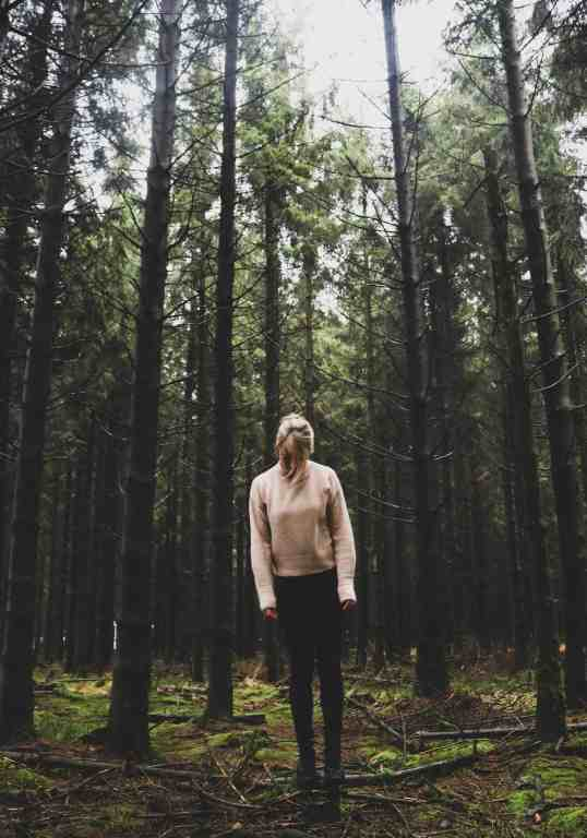 Blonde girl standing in the middle of a forest and high pine trees