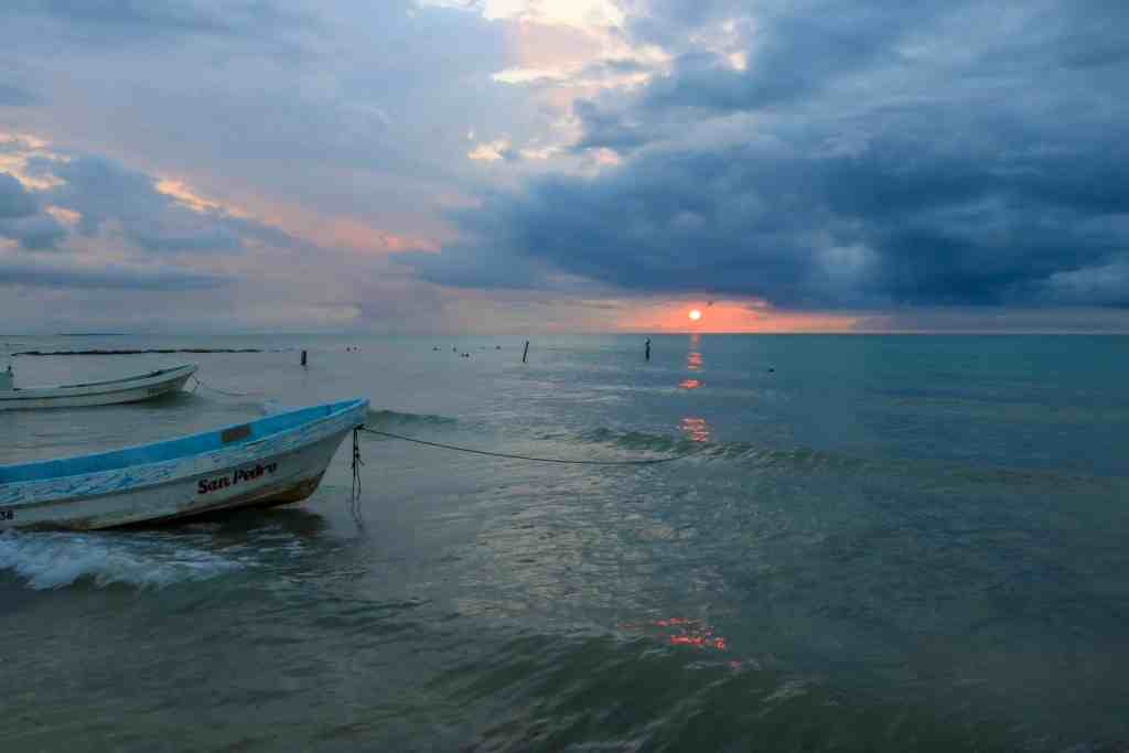 Sunset with dark blue clouds over the ocean and a few boats in the ocean
