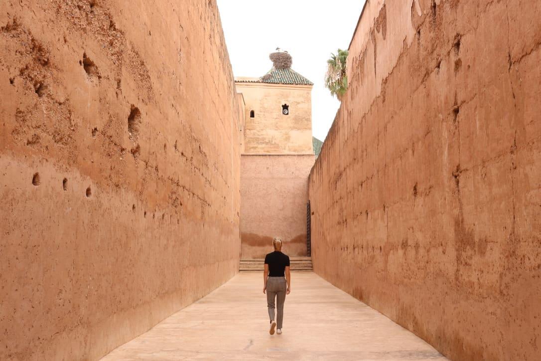 Girl walking between two high orange walls