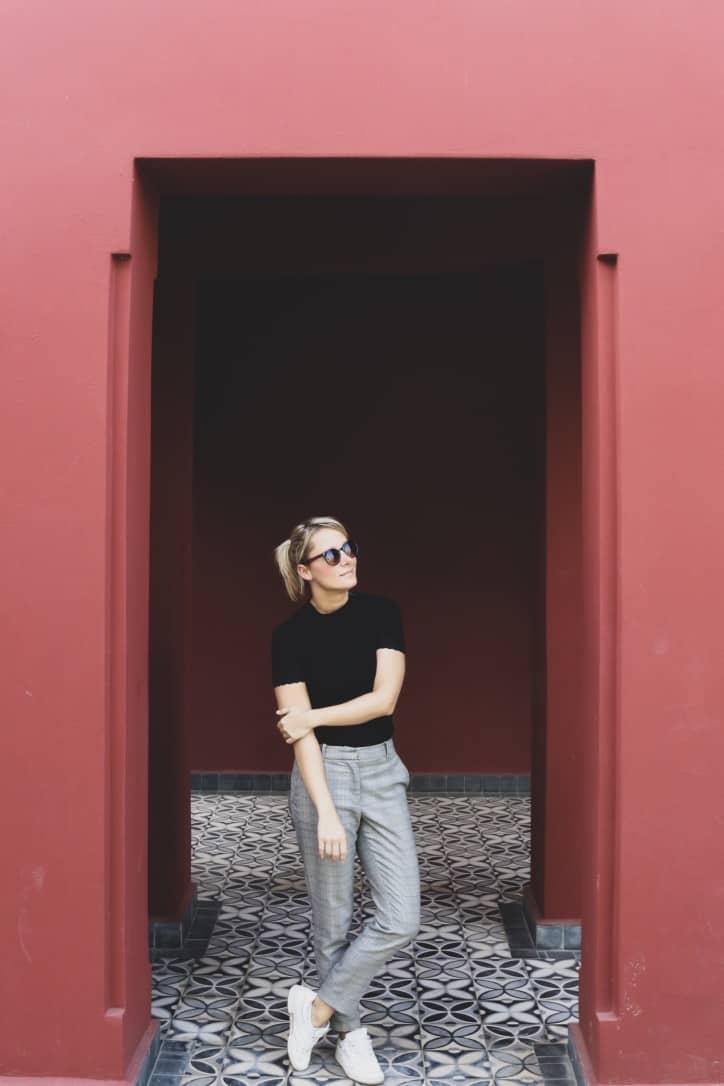 Girl next to brown walls in le jardin secret marrakech